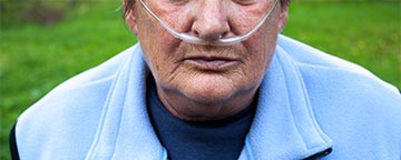 Elderly woman with air going into nose from a tube