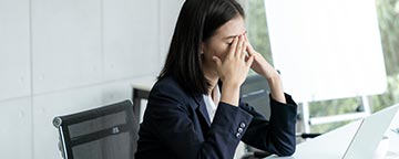 Tired woman in office setting with hands over her eyes