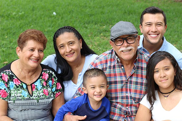 Multi generational family sitting on the grass smiling