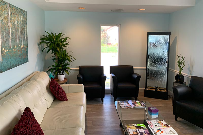 Bradenton Primary Care Doctor waiting room with waterfall, couch, plants, and painting.